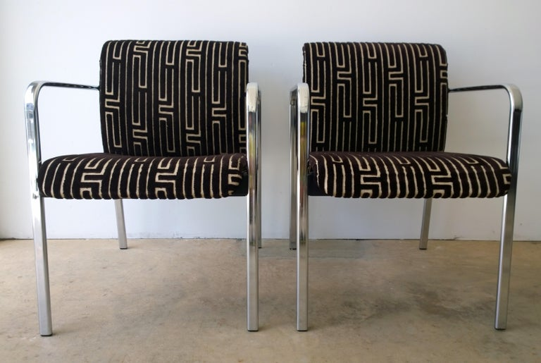 Offered is a pair of vintage Mid-Century Modern Peter Protzman for Herman Miller chrome-plated armchairs with black rubber accents that have been newly upholstered in a burnt-out chocolate brown and tan velvet geometric-Greek key style fabric.