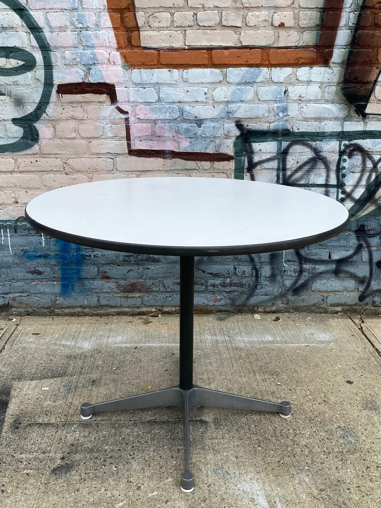 Wonderful example of the Classic Eames dining table for Herman Miller. 36 inch diameter with durable laminate top. Signed and guaranteed authentic. Great for up to 4 people. On sturdy Herman Miller contract aluminum four star base. Pair of Eames