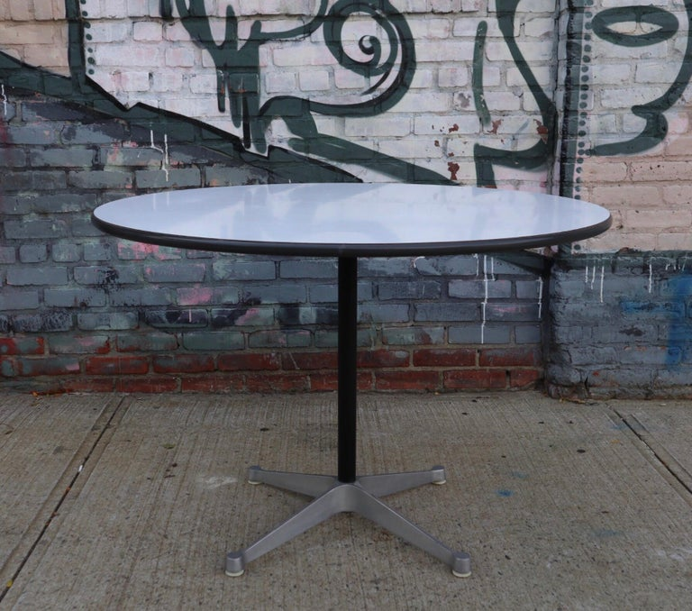Herman Miller Eames dining table. White laminate top in good shape with Herman Miller manufacturer's label underneath. Original screws and footpads. Normal wear. Fits up to 6 chairs. Measures: 48 inch.
