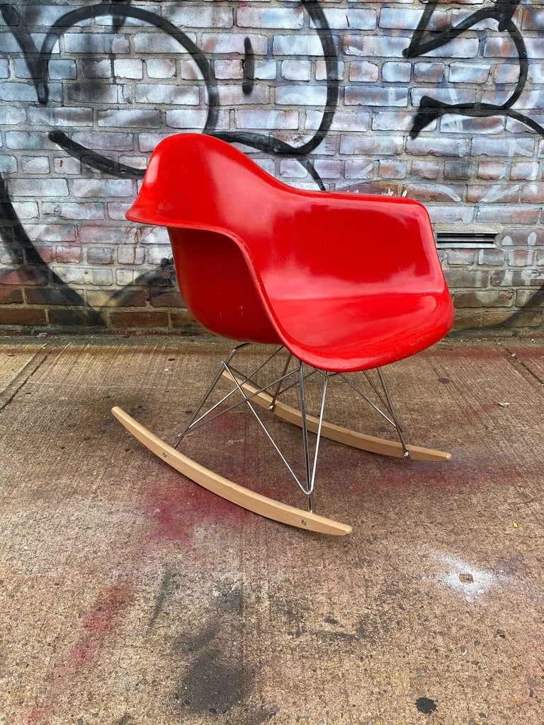 Bright and bold example of the classic design icon. This Eames rocker features a cherry red fiberglass shell, signed Hermon Miller and guaranteed authentic. It presents in very good vintage condition with no breaks. Base comprised of light wood