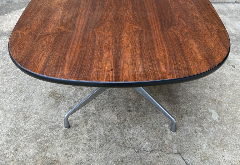 Gorgeous Eames racetrack style table by Herman Miller. Aluminum segmented base and executed in Brazilian rosewood. This was a custom order at the time, and since it is no illegal to produce rosewood furniture (due to environmental regulations) these