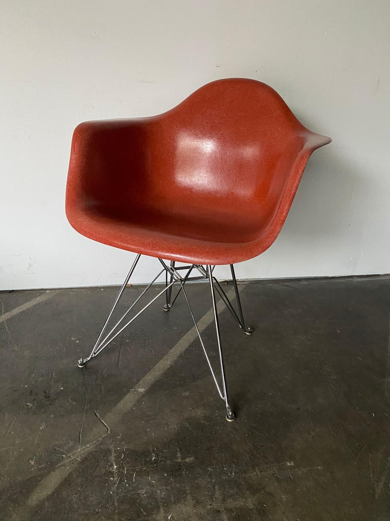 Gorgeous and rare hue of terracotta on this vintage fiberglass Herman Miller Eames armchair. Model DAR with Eiffel base. No cracks. All shock mounts intact. Stamped Herman Miller under chair and guaranteed authentic.