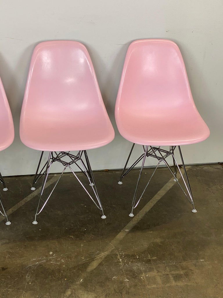 Authentic, signed, vintage Herman Miller Eames dining chairs. Fiberglass shells have been recoated in pink. All chairs signed Herman Miller. All chairs feature new rubber shock mounts for stability and new chrome Eiffel bases. Nylon glides allow for