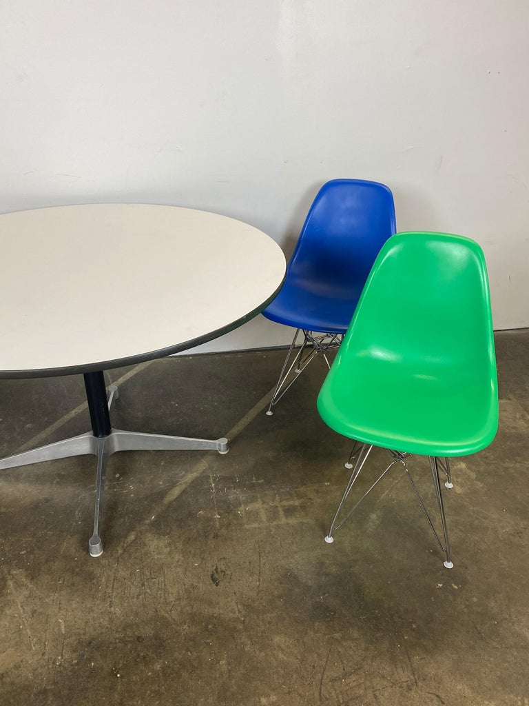 Gorgeous and bright set of Herman Miller Eames dining chairs and table. All authentic Herman Miller. Chairs are vintage but have been color coated in fun colors. New Eoffel bases executed in chrome with nylon glades for same use on multiple