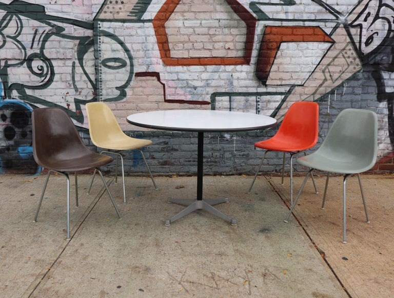 Lovely original Herman Miller Eames dining set. Featuring authentic vintage fiberglass shell chairs in assorted colors and 42 inch diameter dining table. Laminate top in good condition with consistent color. Chairs without cracks or holes. Good