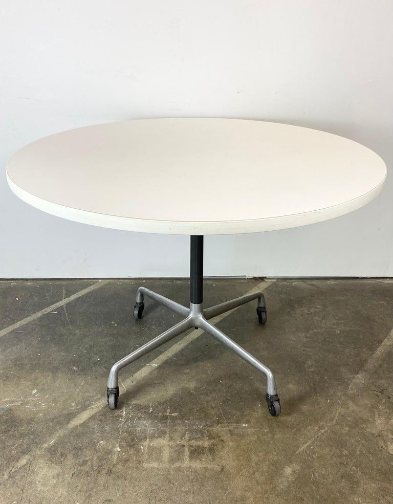Pleased to offer this classic Herman Miller Eames dining table. Circular tabletop, 42 inches in diameter. With white edge and white laminate too. No egregious wear to the surface. Aluminum pedestal base on casters provide an extra utility function