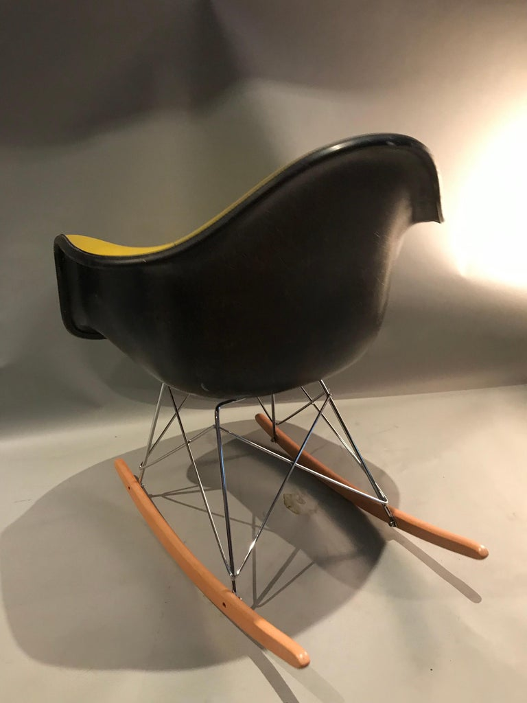 Beautiful Herman Miller Eames fiberglass rocking chair. Herman Miller stamped shell with yellow Naugahyde upholstery. Vintage shell circa 1960s-1970s with newer base.