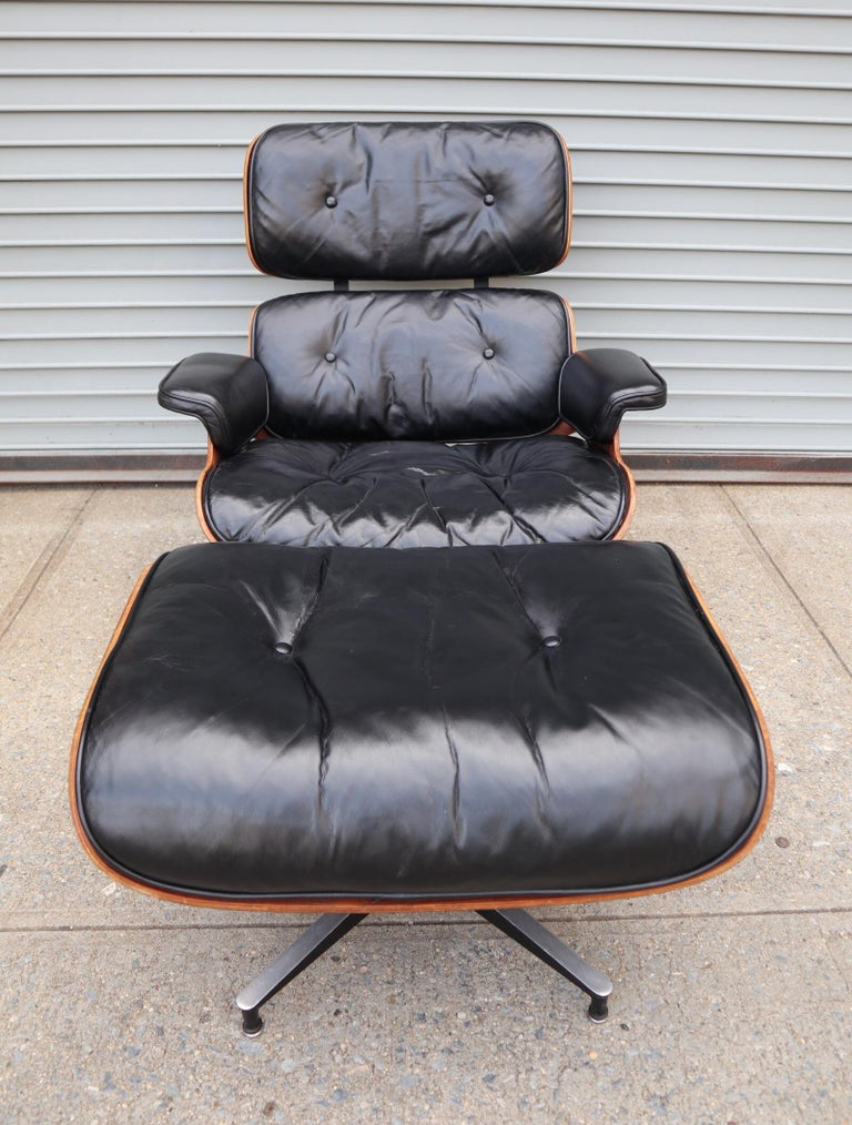 Gorgeous example of the Classic Eames lounge and ottoman. Lovely deep reddish rosewood grains with notable grain pattern and texture. Original chair and ottoman. Black leather cushions in good condition. Chair swivels smoothly. Bases retain all