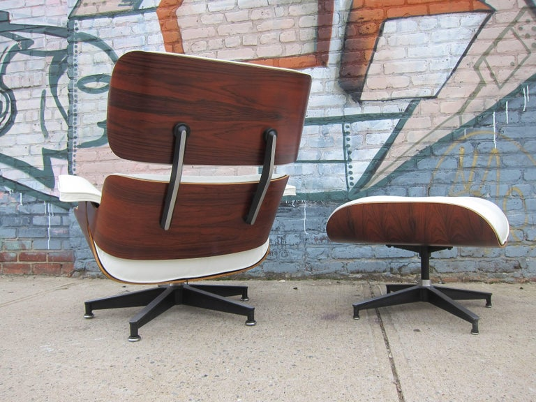 Herman Miller Eames lounge chair and ottoman. Features vintage rosewood shells that have been professionally restored along with perfect new custom made cushions with white leather. Signed Herman Miller. The wood boasts deep and rich colors and