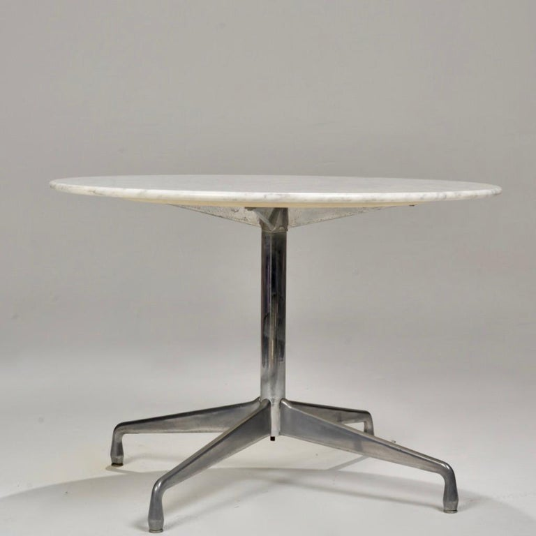This Eames for Herman Miller dining table features a segmented aluminum base and a round Italian Carrara marble top.