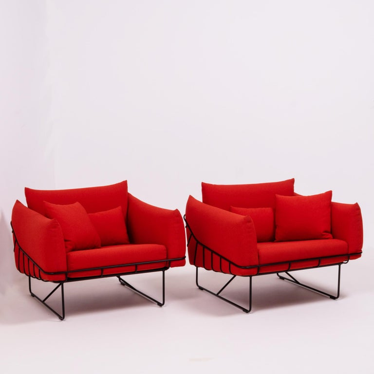 Designed by Sam Hecht and Kim Colin for Herman Miller, this set of Wireframe lounge chairs is bold and contemporary.  The structural black steel wire frame is contrasted by the soft upholstery in a bright red fabric.  Each chair has a separate