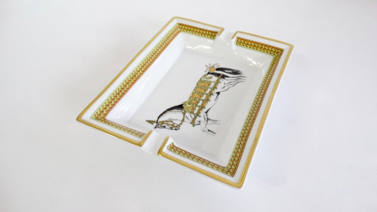 Decorate in style with this amazing Hermés tray! Circa 2000s, this tray is crafted from porcelain and features a decorated cheval horse. Trim is painted in metallic gold and includes a decorative pattern framing the inside. Use to elevate your cigar
