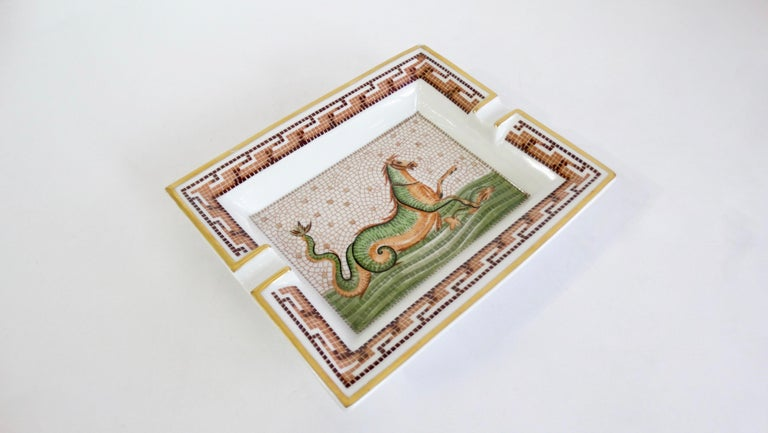 Decorate in style with this amazing Hermés tray! Circa 2000s, this tray is crafted from porcelain and features a mosaic Hippocamp motif derived from Greek mythology. Trim is painted in metallic gold and includes a decorative mosaic pattern framing