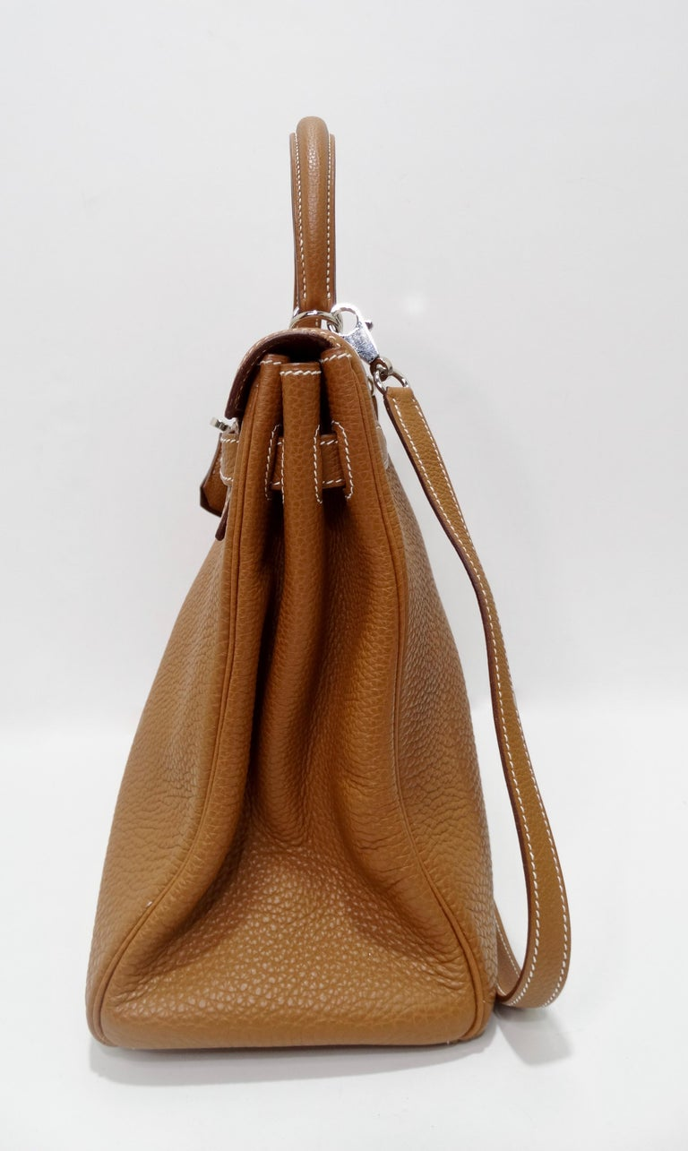 Hello Hermés! Handcrafted by the artisans of Hermes into an iconic 35cm Kelly from 2005. This Hermes Kelly handbag is crafted from togo leather in a beautiful shade of golden brown with Palladium hardware. Features white stitching, single rolled top