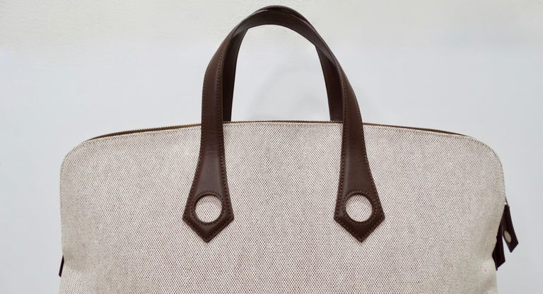 Hello Hermés lovers! Circa 2006, this large travel tote is crafted from tan and brown woven canvas and features pristine chocolate stitching, dual chocolate leather top handles with circle cutouts, tonal leather pipping, silver tone hardware and a