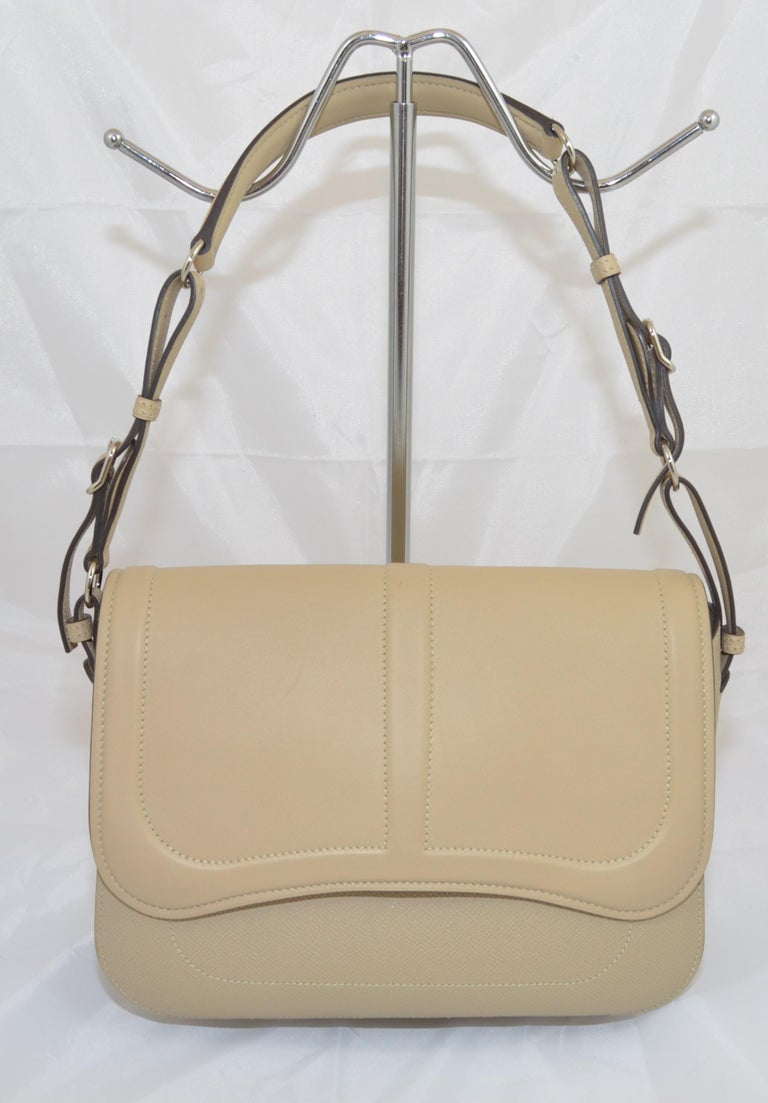 Hermes Harnais khaki-colored shoulder bag features an adjustable leather shoulder strap with polished palladium hardware, and a leather crossover flap. Interior is fully lined in leather with patch pockets. Bag is stamped X (no shape) dating it to