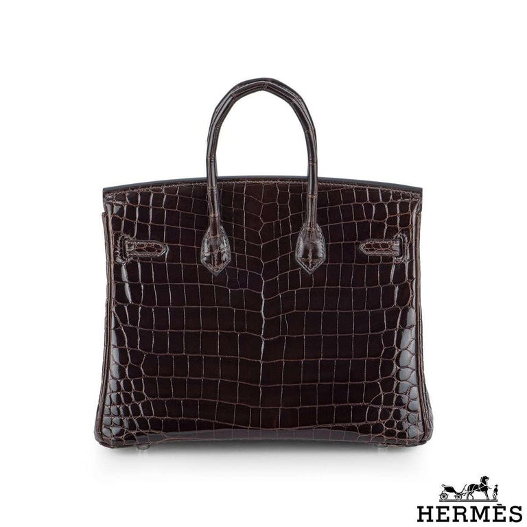 A classic Hermès 25cm Birkin bag. The Cacoan shiny Niloticus Crocodile skin bag is detailed with palladium hardware. The bag has dual rolled top handles complete with padlock and a hanging clochette and keys. The interior features one zipped and one
