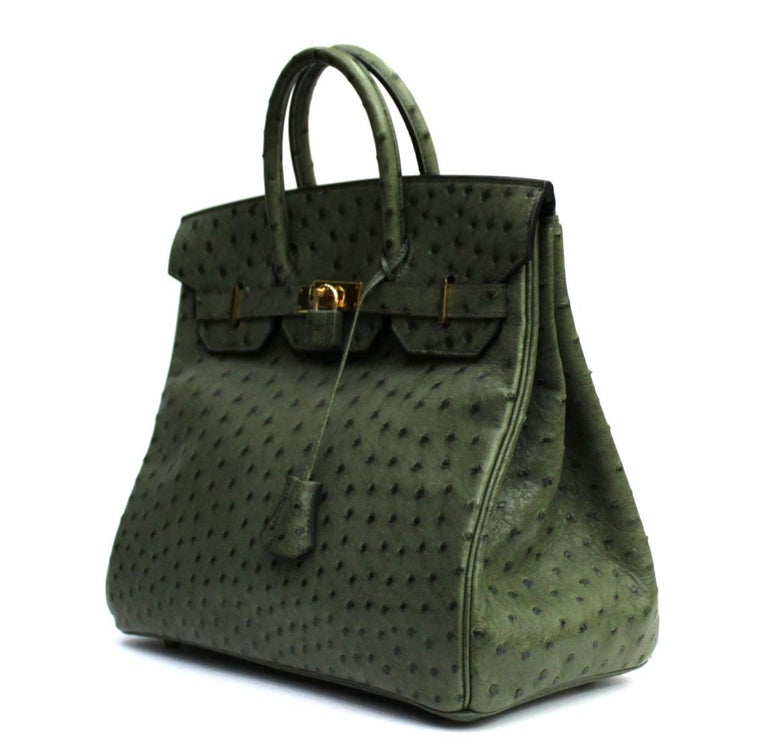 This lovely handbag is crafted of beautifully textured ostrich leather in dark green. The bag features rolled top handles, a crossover flap with a strap closure and gold hardware including a turn lock, a padlock and a hanging clochette with keys.