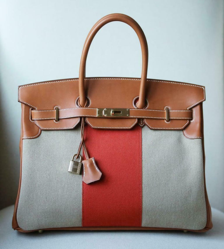 This extremely beautiful Limited Edition Hermès 35cm Flag Barenia Toile Birkin Bag with Permabrass Hardware is a must have for your collection!  The beautiful rich tan leather exterior with orange and neutral toiles well with many pallettes. The bag