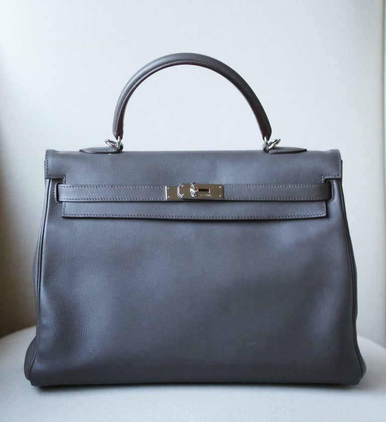 This extremely beautiful Hermès Kelly Retourne 35cm Swift Bag in Etain with Palladium Hardware is a must have for your collection!  The beautiful rich grey-tone exterior of the bag works well with every outfit. Tonal stitching. The bag is crafted