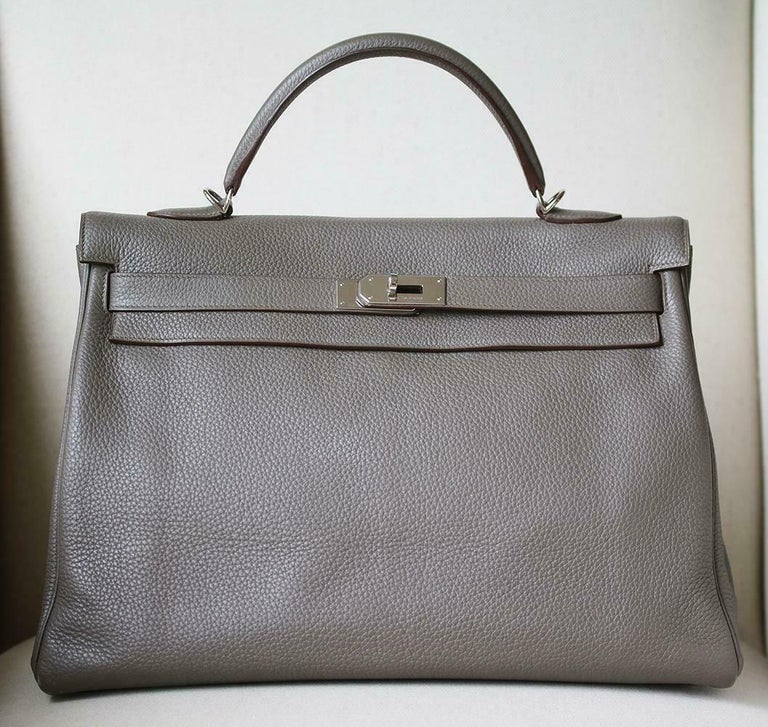 This extremely beautiful Hermès Kelly Retourne 40 Clemence Bag in Etain with Palladium Hardware is a must have for your collection!  The beautiful rich grey-tone exterior of the bag works well with every outfit. Tonal stitching. The bag is crafted
