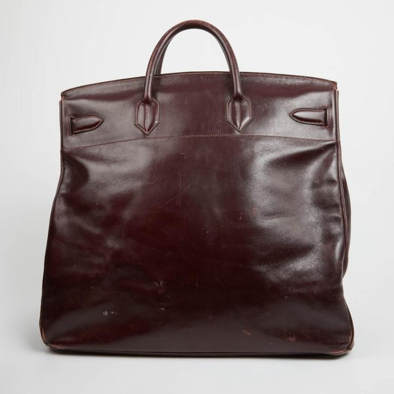 Big brother of the inevitable Birkin, this vintage Courroies Top is in dark burgundy box leather, size 45. It was originally designed to make life easier for riders, then declined in handbag format in the 80s This large bag has its padlock, bell,