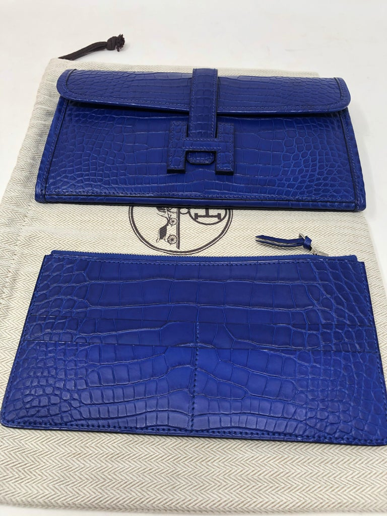 Hermes Crocodile Bleu Electrique Jige Duo Wallet. Hermes long wallet in matte Alligator. Can be worn as an evening or day clutch. Includes insert for holding cards, etc. Never used. Stayed in the box. Purchased at Hermes $20,200. Includes dust cover