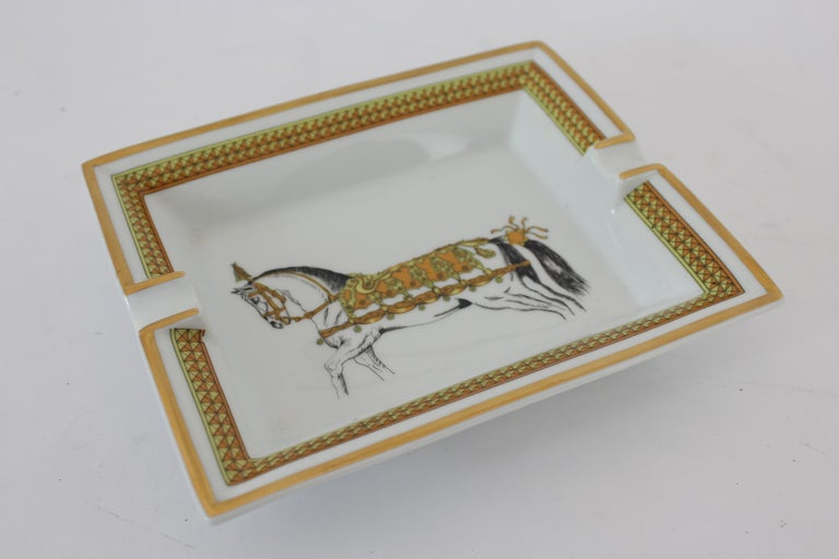 Hermes vintage ashtray 90s. French porcelain, color white and gold with a horse depicted. On the bottom velvet of goat. Made in France. Excellent vintage conditions.  Measures: 19 x 15.5 cm