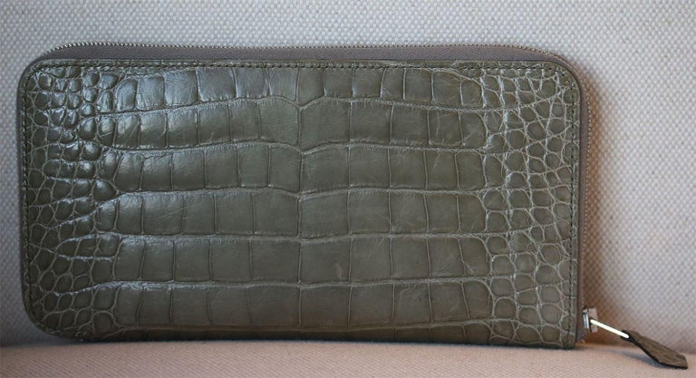 Wallet in crocodile skin, silver- and palladium-plated zip. Inside: ten credit card slots and a zippered change pouch.  Dimensions: Approx. 11 x 20 x 1.5 cm   Condition: Slight marks to the leather; see pictures. Otherwise, no sign of wear.