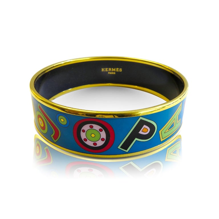 This Hermes bangle features an 18 Karat gold plated with a printed enamel. Carved in Austria, It weighs 41.6 grams, 20mm wide and has an inner diameter of 2.7 inches to give a comfortable fit in your wrist.  Condition: Excellent