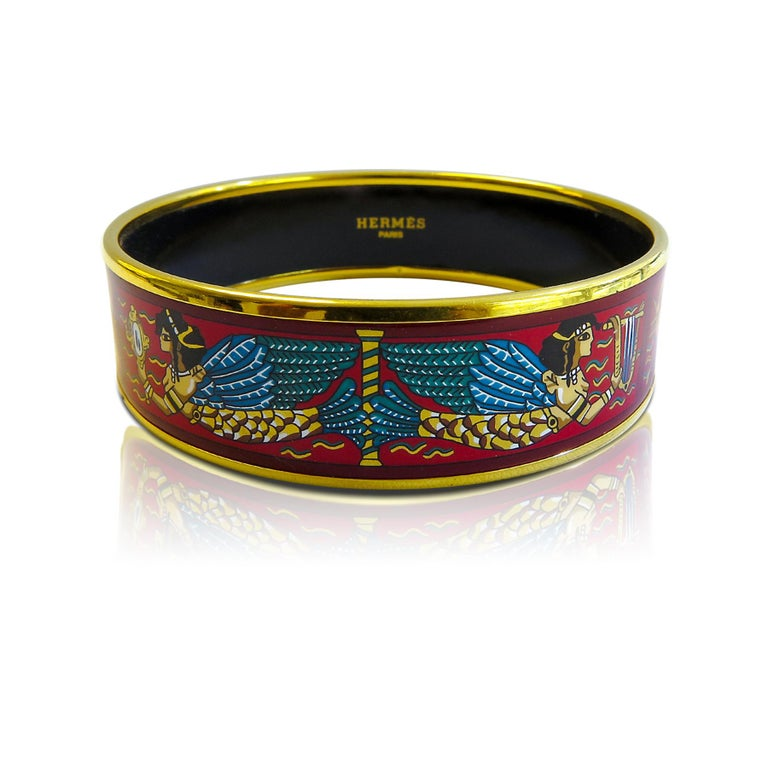 This Hermes bangle features an18 Karat gold plated with a printed enamel. Carved in Austria, It weighs 40.8 grams, 20mm wide and has an inner diameter of 2.5 inches to give a comfortable fit in your wrist.  Condition: Excellent