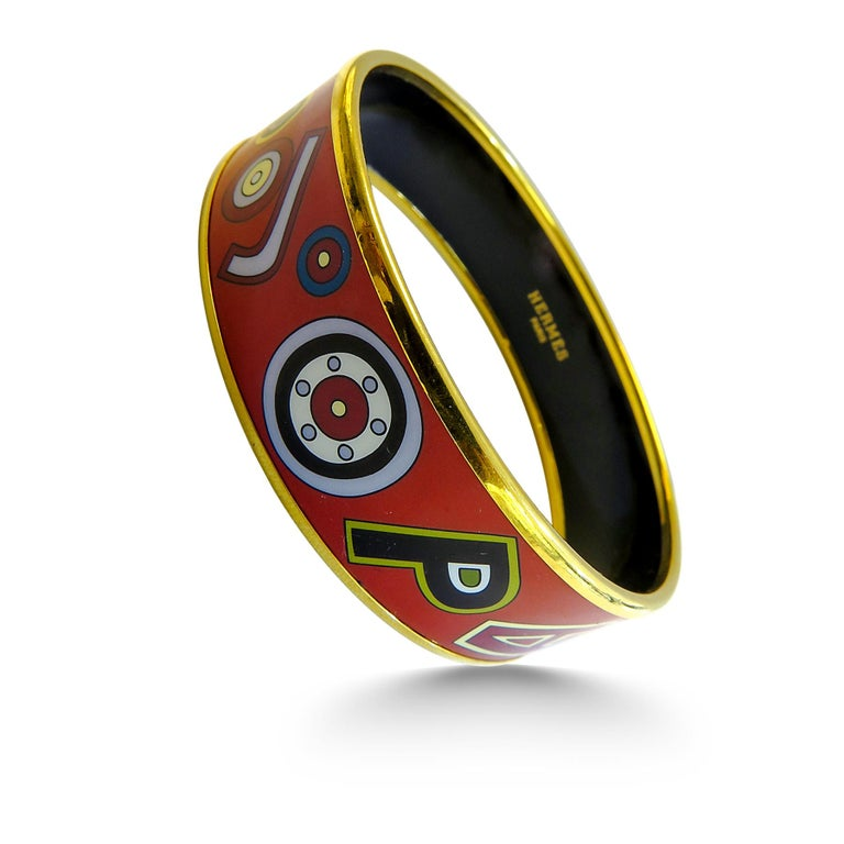 This Hermes bangle features an18 Karat gold plated with a printed enamel. Carved in Austria, It weighs 44 grams, 20mm wide and has an inner diameter of 2.5 inches to give a comfortable fit in your wrist.   Condition: Excellent