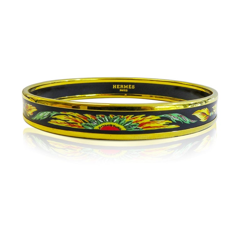 This Hermes bangle features an 18 Karat gold plated with a printed enamel. Carved in Austria, It weighs 22.9 grams, 10mm wide and has an inner diameter of 2.7 inches to give a comfortable fit in your wrist.  Condition: Excellent ( There is small