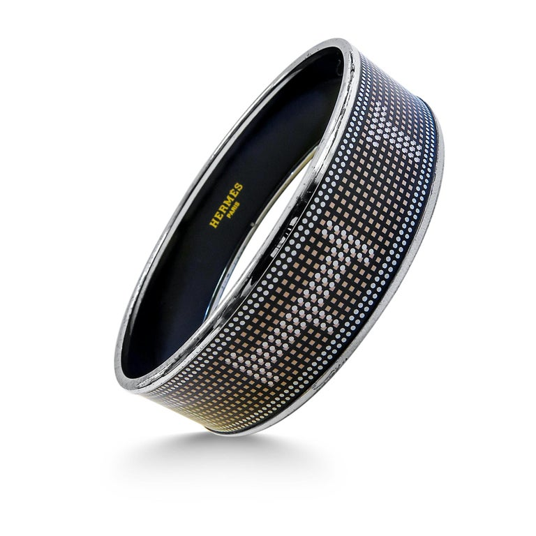 This Hermes bangle features platinum plated with a printed enamel. Carved in Austria, It weighs 39.4 grams, 20mm wide and has an inner diameter of 2.5 inches to give a comfortable fit in your wrist.