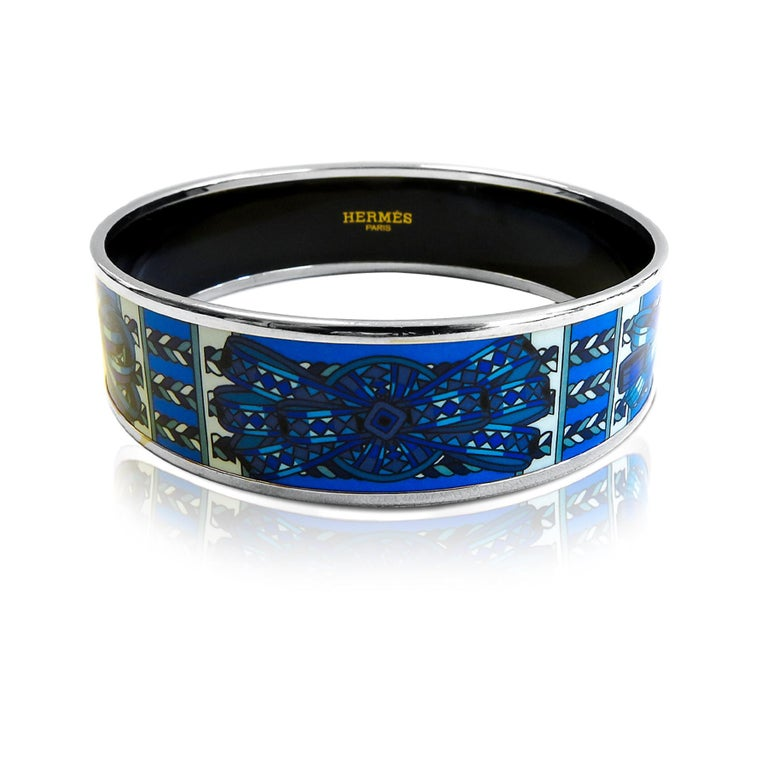 This Hermes bangle features platinum plated with a printed enamel. Carved in Austria, It weighs 38 grams, 20mm wide and has an inner diameter of 2.5 inches to give a comfortable fit in your wrist. Condition: Excellent