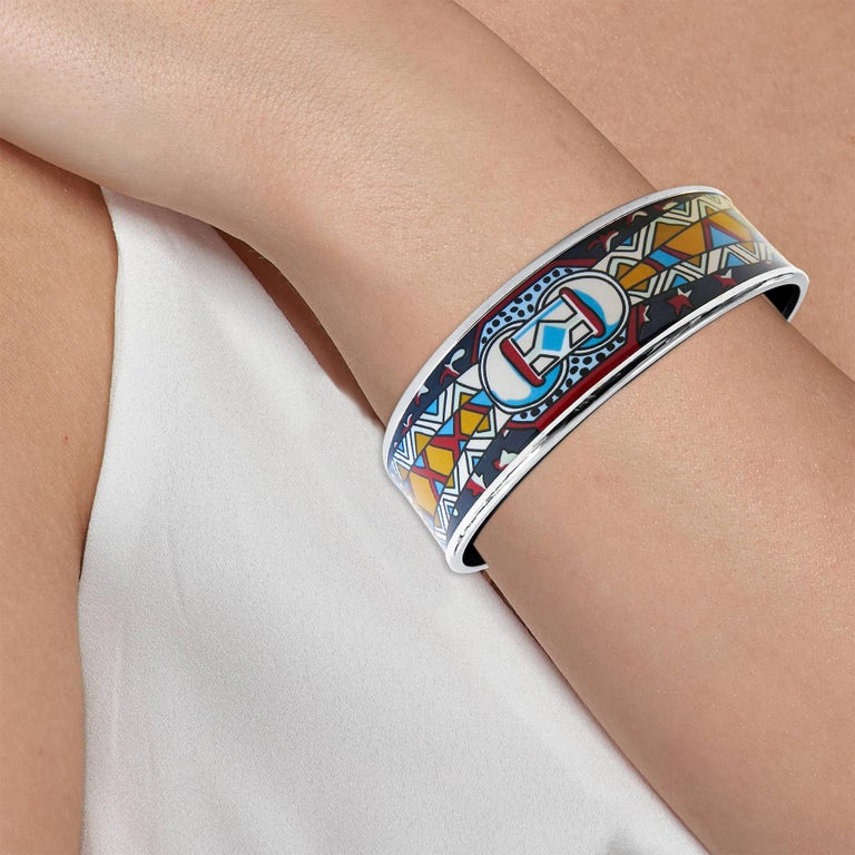 This Hermes bangle features a platinum-plated with a printed pattern enamel. Carved in Austria, It weighs 36.8 grams, 20mm wide and has an inner diameter of 2.8 inches to give a comfortable fit in your wrist.  Condition: Excellent