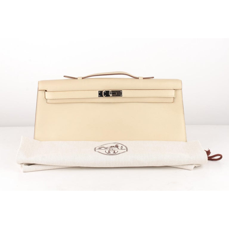 Hermes Beige Leather Kelly Cut Clutch Bag Pochetteù  SHOPIFY Title: Kelly Cut Clutch Bag  Material: Leather Color: Beige Model: Kelly Cut Gender: Women, Men Country of Manufacture: France Size: Medium Bag Depth: 1 inches - 2,5 cm  Bag Height: 5