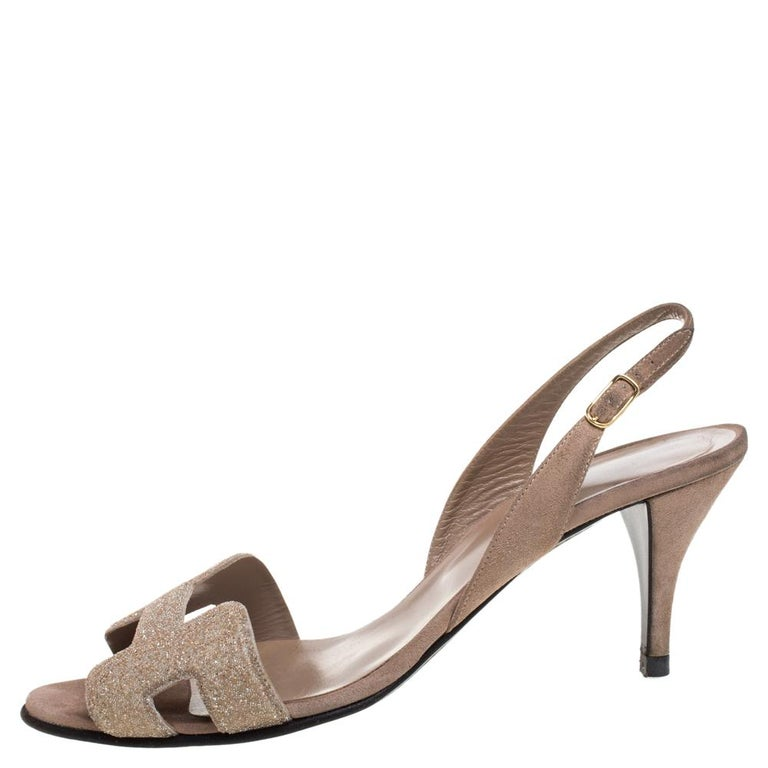 These Night sandals from Hermes speak of beauty in a minimal yet appealing way! They come crafted from beige suede and styled with the signature 'H' shaped vamp straps that are sprinkled with crystal powder. They are equipped with buckled slingbacks