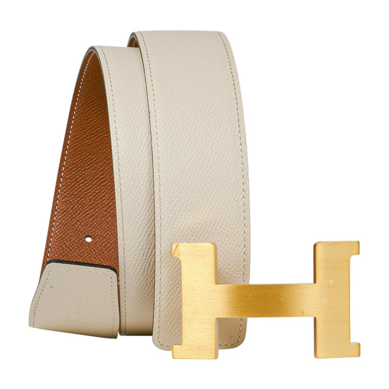 Guaranteed authentic Hermes Constance 42 mm belt features reversible Gold to Craie Epsom Leather.   Fabulous over sized brushed Gold signature H buckle.   Now a retired size, this is sure to become a collectors treasure.  Signature HERMES PARIS MADE