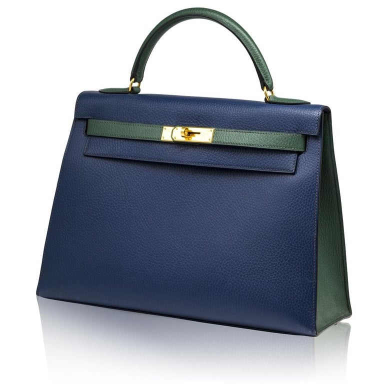 Adding a twist to the traditional Hermès Kelly, this Limited Edition Bi-colour rarity, crafted in epsom leather, features two assorted colours across its silhouette; a navy blue body and forest green handles and belt arms, which are both offset by