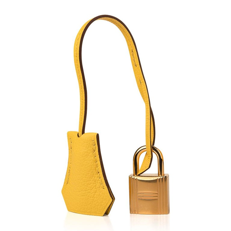 Guaranteed authentic Hermes Birkin 25 bag features Jaune de Naples in Novillo leather.  Bull leather, Taurillion Novillo has a far finer grain than Clemence or togo, and is lighter in weight. Colours have rich saturation and colours are clear with