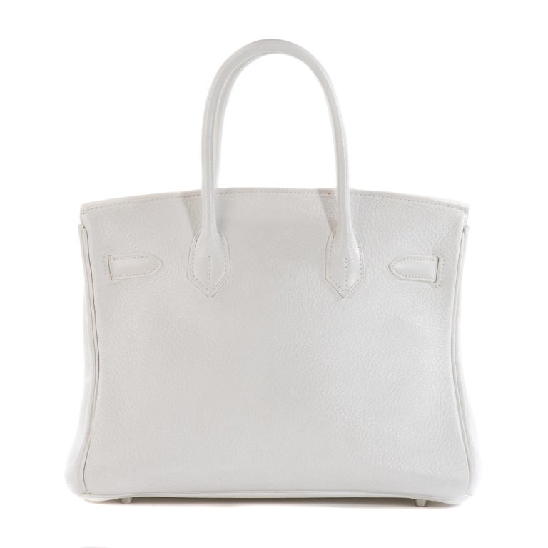 The iconic Hermes Birkin 30 cm handbag in white togo leather, palladium metal hardware, double gold leather handle for hand carrying.  Inner lining in gold leather, a zipped pocket, a patch pocket. Sold with zipper, key, padlock, bell. Signature: