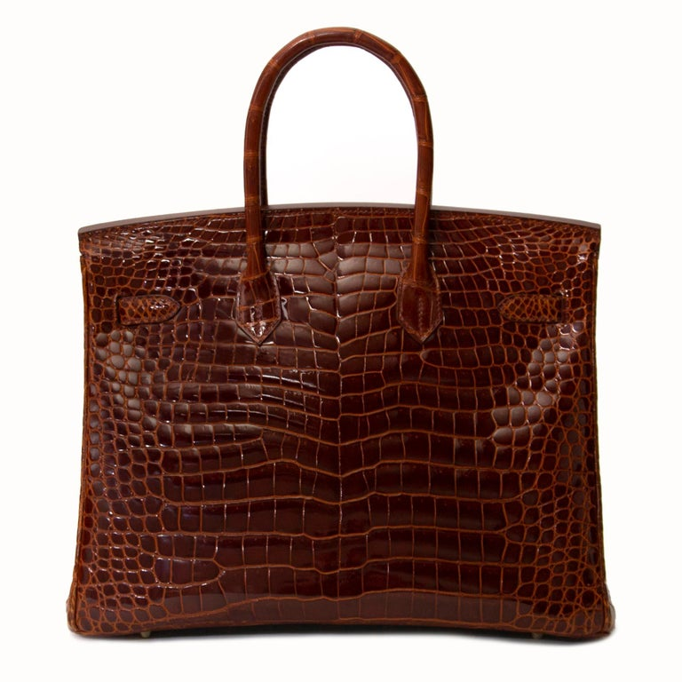 This exotic Hermès Birkin 35 is as exclusive as it is elusive. The Crocodile Porosus leather is colored in a warm and rich brown, called 'Havane'.  The bag has gold toned hardware, making it a wonderfully luxurious combination. This beauty in