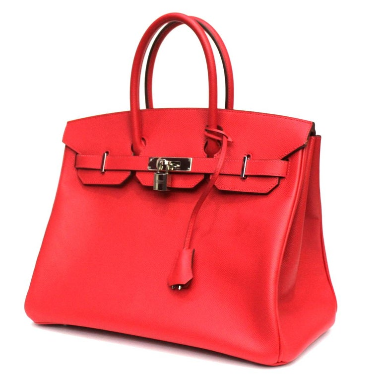 This Hermès Birkin 35cm bag is featured in the Rouge Casaque color, which is a red tone. This bag is made from smooth Epsom leather, which is highly resistant to scratching. The blind stamp on this store-fresh Hermès bag is