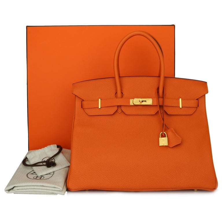 Hermès Birkin 35cm Bag Orange Togo Leather with Gold Hardware Stamp R Year 2014.  This bag is still in brand new condition. The leather still smells fresh as when new, along with it still holding to the original shape. The hardware still very shiny