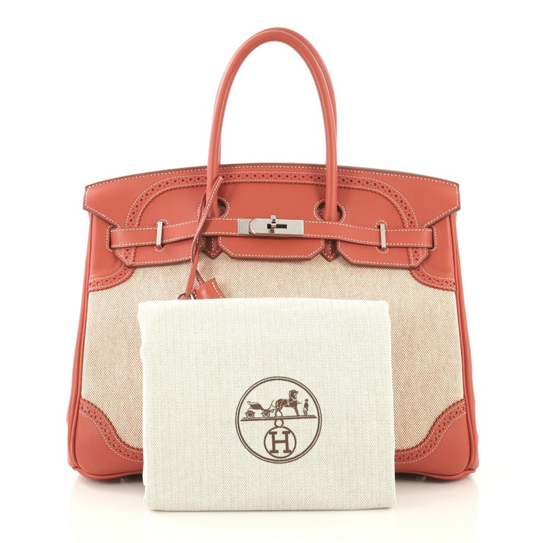 This Hermes Birkin Ghillies Handbag Toile and Sanguine Swift with Palladium Hardware 35, crafted from Sanguine Toile H and Swift leather, features dual rolled handles, frontal flap, decorative perforations and palladium hardware. Its turn-lock