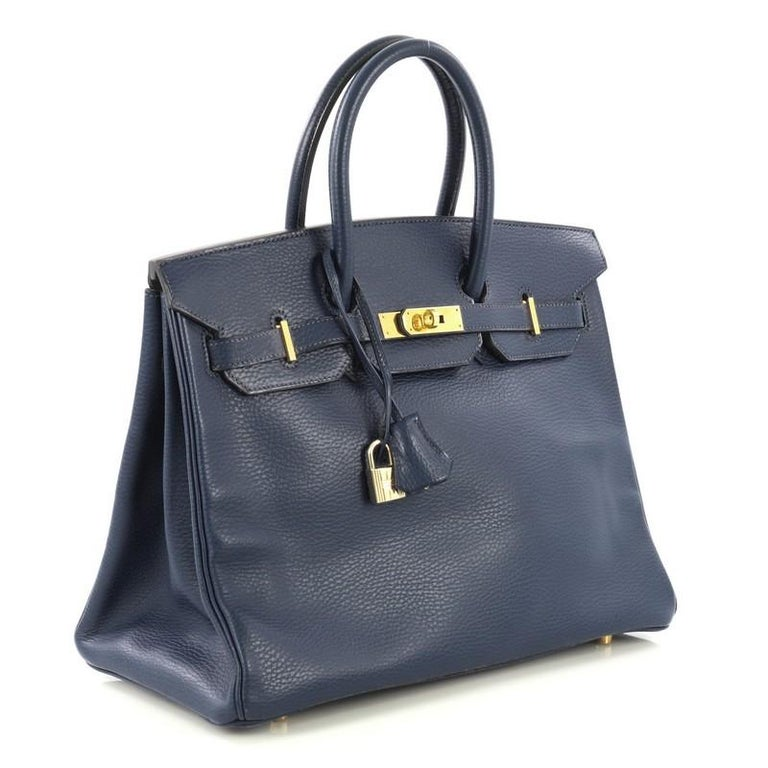 This Hermes Birkin Handbag Bleu Saphir Ardennes with Gold Hardware 35, crafted in Bleu Saphir blue Ardennes leather, features dual rolled handles, frontal flap, and gold hardware. Its turn-lock closure opens to a Bleu Saphir blue Chevre leather