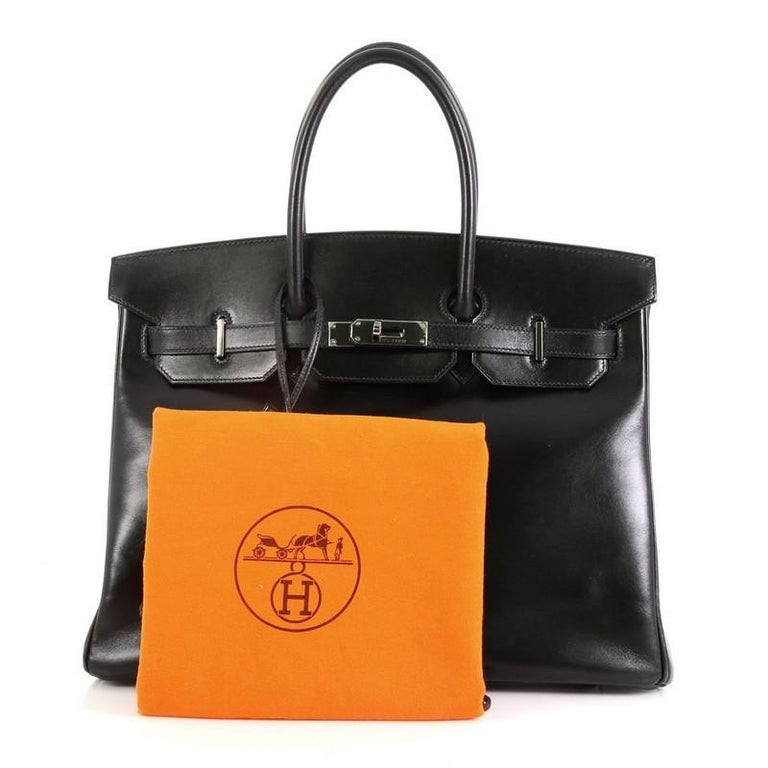 This Hermes Birkin Handbag Noir Box Calf with Palladium Hardware 35, crafted in Noir black Box Calf leather, features dual rolled handles, frontal flap, and ruthenium hardware. Its turn-lock closure opens to a Noir black Chevre leather interior with
