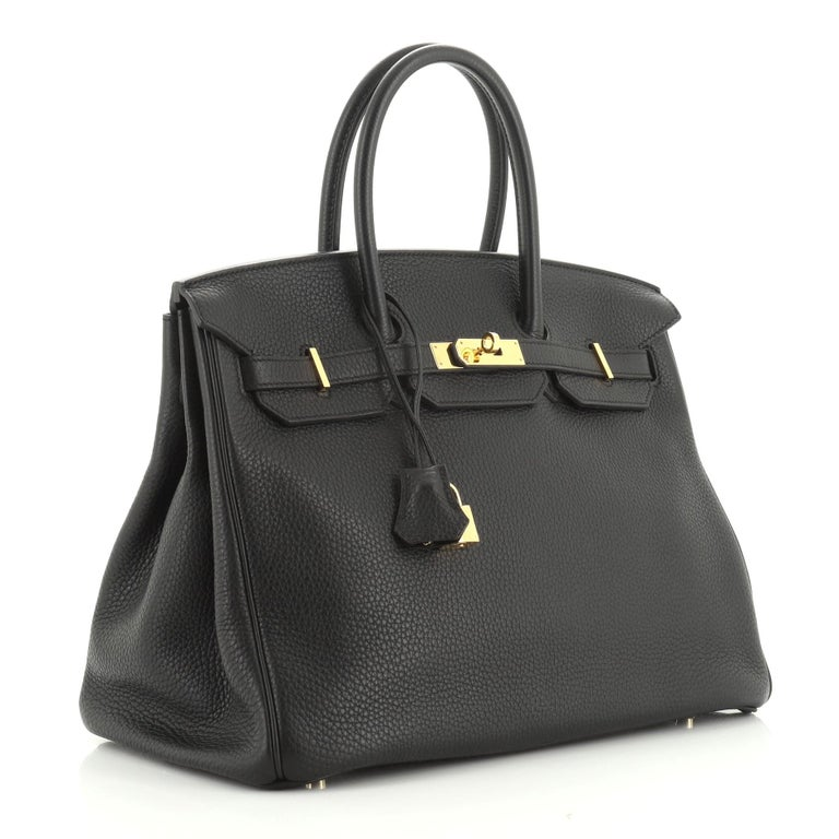 This Hermes Birkin Handbag Noir Clemence with Gold Hardware 35, crafted in Noir black Clemence leather, features dual rolled handles, frontal flap, and gold hardware. Its turn-lock closure opens to a Noir black Chevre leather interior with zip and