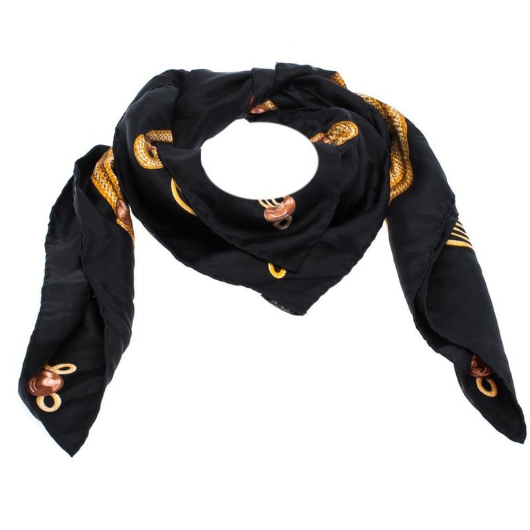 Get a distinctive look with this elegant scarf from Hermes. The twill scarf has been woven from 100% silk, This luxurious scarf comes in stunning shades of black and gold and flaunts a marvellous Brandebourgs pattern. Wear it with your work attire